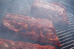 Ribs cooking in the smoker. Royalty Free Stock Photo