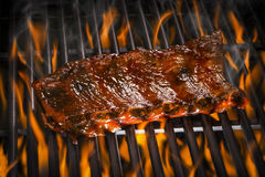 Ribs on a Flaming Hot Grill. Barbecued pork spare ribs on a flaming hot grill Stock Image