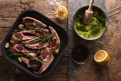 Ribs of lamb in saucepan and mashed potatoes and peas in a ladle Royalty Free Stock Photos
