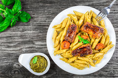 Ribs with pasta penne, carrots and the pesto sauce on an old woo Royalty Free Stock Photos