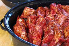 Ribs piled into a black roaster for slow cooking.  stock photo