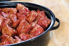 Ribs piled into a black roaster for slow cooking.  royalty free stock photos