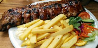 Ribs with potatoes. Tasty dish with pork ribs, fri potatoes and salad royalty free stock photo