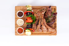 Ribs with rosemary and vegetable barbecue grill, sauces  wooden board  white background menu Royalty Free Stock Image