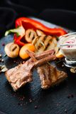 Ribs with sauce and salad. Ribs with sauce on black plate with pepper and onion salad with herbs and spices Stock Photo