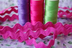 Ric rac with colorful spools of thread in purple, pink and green royalty free stock photography
