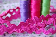Ric rac with colorful spools of thread in purple, pink and green royalty free stock image
