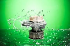 Ricambi auto, pompa di raffreddamento del motore nella spruzzata dell'acqua sul backgro verde Fotografie Stock Libere da Diritti