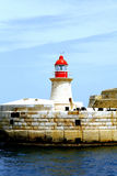 Ricasoli Lighthouse, Grand Harbour, Malta. The Ricasoli lighthouse at the entrance to the Grand Habour, Malta on the breakwater, colored red to demark Maritime Stock Photography