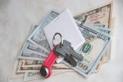 Ricchezza e ricchezze rappresentate da denaro contante e dalle chiavi chiavi dell'appartamento dei dollari chiave di scambio del  immagini stock