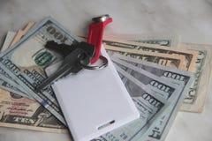 Ricchezza e ricchezze rappresentate da denaro contante e dalle chiavi chiavi dell'appartamento dei dollari chiave di scambio del  immagine stock libera da diritti