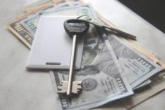 Ricchezza e ricchezze rappresentate da denaro contante e dalle chiavi chiavi dell'appartamento dei dollari chiave di scambio del  immagini stock libere da diritti