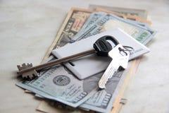 Ricchezza e ricchezze rappresentate da denaro contante e dalle chiavi chiavi dell'appartamento dei dollari chiave di scambio del  fotografie stock libere da diritti