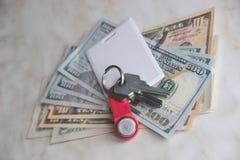 Ricchezza e ricchezze rappresentate da denaro contante e dalle chiavi chiavi dell'appartamento dei dollari chiave di scambio del  immagine stock
