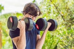 Ricciolo del bicipite - pesi l'uomo di forma fisica di addestramento fuori del risolvere il braccio fotografia stock