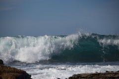 Ricciolo delle onde che guardano fuori dalle rocce Fotografie Stock