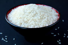 Rice. White rice in a cup of black on black background Stock Photography