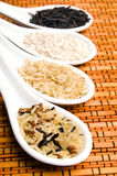 Rice. Various kinds of rice - jasmine rice, white rice, black rice, wild rice in white spoons over bamboo background Royalty Free Stock Photography