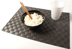 Rice. On white background and black placemat Royalty Free Stock Photography