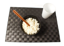 Rice. On white background and black placemat Royalty Free Stock Photos
