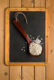 Rice Arborio in a wooden spoon on a chalkboard. Rice Arborio in a wooden spoon on a small chalkboard Stock Images