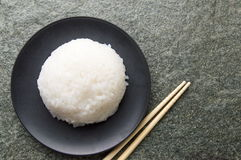 Rice ball and chopsticks. Ball of rice in a black plate with chopsticks stock photo