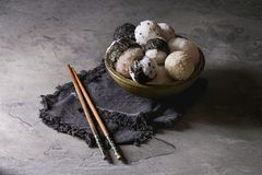 Rice balls and eggs. Bowl with different size rice balls with black sesame and seaweed nori, served with soft boiled eggs, soy sauce, chopsticks over gray table Stock Images