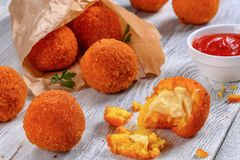 Rice balls stuffed with cheese in paper cornet. Delicious hot italian arancini - saffron rice balls stuffed with cheese in paper bag on old wooden table with Royalty Free Stock Image