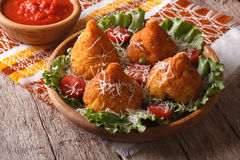 Rice balls stuffed with meat and tomato sauce closeup. horizonta. Arancini rice balls stuffed with meat and tomato sauce closeup on a table. horizontal Royalty Free Stock Photo