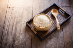 Rice in bamboo basket and wooden spoon on sack bag and wooden ba Royalty Free Stock Photo