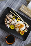 Rice, bamboo and seafood on black plate Stock Photography