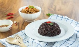 Rice berry in a plate and stir-fried minced pork basil in a bowl on a wooden table. Rice berry in a dish and stir-fried pork basil in a bowl and chili fish sauce stock photo