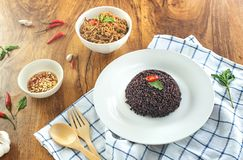 Rice berry in a plate and stir-fried minced pork basil in a bowl on a wooden table. Rice berry in a dish and stir-fried pork basil in a bowl and chili fish sauce royalty free stock photos