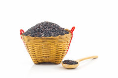 Rice berry in a wooden spoon and basket. Stock Photos