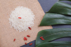 Rice  on black stone table with khaki linen and green le Royalty Free Stock Photo