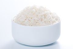 Rice in a bowl. On a white background Stock Photos