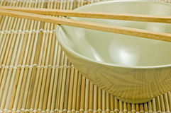 Rice bowl on bamboo mat with chopsticks Royalty Free Stock Photography