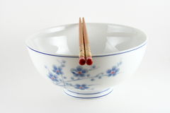 Rice bowl and chopsticks. Pair of chopsticks lying on top of rice bowl with floral design, white background stock image
