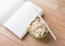 Rice a bowl with chopsticks and a book rests on a wooden desk. Royalty Free Stock Images
