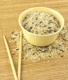 Rice, bowl and chopsticks. China color rice and beige bowl on brown straw mat with chopsticks closeup royalty free stock photography