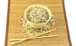 Rice, bowl and chopsticks. China color rice in beige bowl on brown straw mat with chopsticks isolated on white closeup stock image