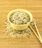 Rice in bowl and chopsticks on starw mat. China color rice in yellow bowl and chopsticks on brown straw mat closeup vertical photo stock images