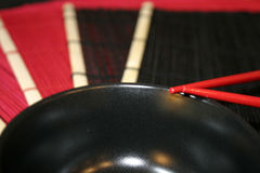 Rice Bowl and Mats. Red and black bamboo straw mats with black rice bowl and red chopsticks Stock Photo