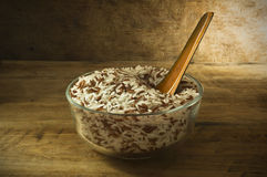 Rice in a bowl placed on the old wooden floor low key light. Royalty Free Stock Photos