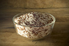 Rice in a bowl placed on the old wooden floor low key light. Stock Images