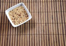 Rice. Bowl of raw rice on bamboo tablecloth background Stock Images