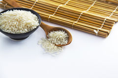 Rice in bowl with spoon. And bamboo mats behind them Royalty Free Stock Photo