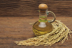 Rice bran oil. In bottle glass with seed and bran on the old plank wood Stock Image