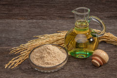 Rice bran oil. In bottle glass with seed and bran on the old plank wood Stock Photo