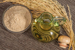 Rice bran oil. In bottle glass with seed and bran on the old plank wood Royalty Free Stock Image